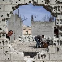 Boys play near the remains of damaged buildings in the rebel-held town of Douma in the eastern Damascus suburb of Ghouta, Syria, on Saturday. | REUTERS