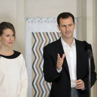 Syrian President Bashar Assad stands next to his wife, Asma, as he addresses injured soldiers and their mothers during a celebration marking Syrian Mother's Day in Damascus on Monday. | REUTERS