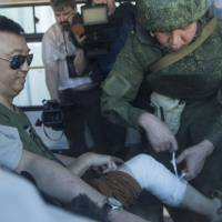 A Chinese reporter is bandaged by a Russian military officer after he fell while moving to safety during explosions in Kinsibba, Syria, near the border with Turkey Tuesday. A series of artillery shells exploded on the main street of the village of Kinsibba on Tuesday, sending a group of visiting international reporters running for cover and underscoring the limits of Syria's partial cease-fire. | AP