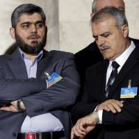 Asaad Al-Zoubi of the High Negotiations Committee (HNC) looks at his watch next to Mohamed Alloush of the Jaysh al Islam during a news conference after a meeting with U.N. mediator for Syria Staffan de Mistura during Syria peace talks at the United Nations in Genevaon March 15. | REUTERS