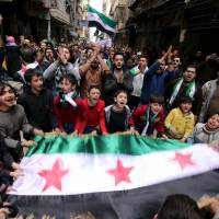 Protesters shout slogans and carry Free Syrian Army flags during an anti-government protest in the al-Sukari neighborhood of Aleppo on Friday. | REUTERS