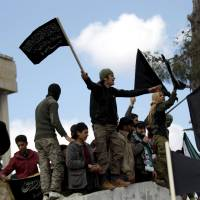 Protesters wave Nusra Front flags and shout slogans during an anti-government demonstration following religious services in the town of Marat Numan, in Idlib province, Syria, on Friday. | REUTERS