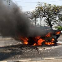 A Ford Fiesta burns after it was slammed into by a black Mercedes, killing it's two occupants on a Thai highway on March 13. The smaller car burst into flames and the couple inside, both graduate students in their 30s, died at the scene of the accident. | SENIOR SGT. MAJ. PARICHART PANGRITH VIA AP