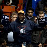An anti-Donald Trump protester tears up a campaign sign before a rally for the Republican presidential front-runner at the University of Illinois at Chicago Pavilion in Chicago on Friday was cancelled. | AFP-JIJI