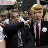 A supporter for Democratic presidential candidate Sen. Bernie Sanders gives the thumbs down sign to a fellow Sanders' supporter wearing a Donald Trump mask during a campaign rally Saturday in Phoenix.   AP