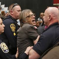 Photojournalist Christopher Morris is escorted by police during the rally of Republican presidential candidate, Donald Trump Monday at Radford University in Radford, Virginia. | AP