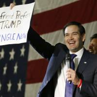 Republican presidential candidate Sen. Marco Rubio holds up an anti-Trump sign during a rally in Oklahoma City, Monday. At rear is former Louisiana Gov. Bobby Jindal. | AP