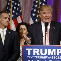 Donald Trump's campaign manager, Corey Lewandowski, listens as Trump speaks in Palm Beach, Florida, on March 15. | AP