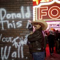 Protesters targeting Republican U.S. presidential candidate Donald Trump gather outside a Republican presidential debate site in Detroit Thursday. | REUTERS