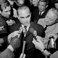 Reporters surround presidential candidate former Alabama Gov. George Wallace at Metro Airport in Detroit in 1968 after the presidential candidate arrived to address a night rally at Cobo Hall. Donald Trump promises to 'Make America Great Again.' George Wallace said he would 'Stand up for America.' The 2016 Republican presidential front-runner doesn't say he's following the 1960s playbook of the Alabama segregationist, a four-time presidential hopeful. | AP