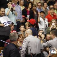 Supporters of U.S. Republican presidential candidate Donald Trump heckle a black demonstrator as he is removed from a campaign rally in Fayetteville, North Carolina, March 9. Trump was interrupted repeatedly by demonstrators during his rally. | REUTERS