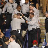 Police officers forcibly restrain a protester at U.S. Republican presidential candidate Donald Trump's campaign rally in Fayetteville, North Carolina, March 9. | REUTERS
