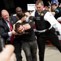 Secret Service agents detain a man following a disturbance at Dayton International Airport in Dayton, Ohio, on Saturday as U.S. Republican presidential candidate Donald Trump addressed supporters. | REUTERS