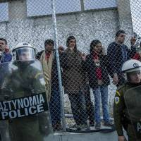 Greek police stand guard in front of the Moria camp while refugees demonstrate against the new deal between the EU and Turkey, on March 24 in Lesbos. Greece. | AFP-JIJI
