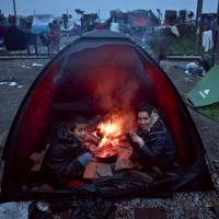 Migrants sit next to a fire they started inside a tent to cover it from rainfall at the northern Greek border point of Idomeni, Greece, Tuesday. | AP