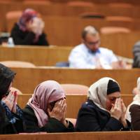 Members of the audience pray Wednesday during a moment of silence as a tribute following the attacks in Brussels on Tuesday, at a Ahmadiyya Muslim Community of Metro Detroit symposium in Dearborn, Michigan. | AP