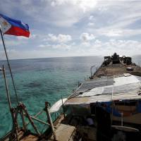 A Philippine flag flutters in March 2014 aboard the remains of the BRP Sierra Madre, a dilapidated Philippine Navy ship that was run aground in 1999 and became a Philippine military detachment on the disputed Second Thomas Shoal, part of the Spratly Islands, in the South China Sea. | REUTERS