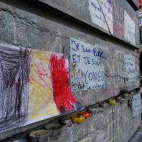 A Belgian flag on paper appears Sunday next to a message reading 'I am Brussels and I am Congo, stop violence' at the makeshift memorial outside the stock exchange in Brussels at an area that has become an unofficial shrine to victims of the March 22 terror attacks claimed by the Islamic State group. | AFP-JIJI