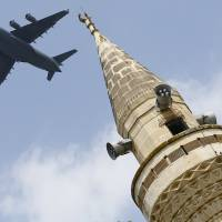 A U.S. Air Force Boeing C-17A Globemaster III large transport aircraft flies over a minaret after taking off from Incirlik air base in Adana, Turkey, in August. The U.S. has ordered families of military and diplomatic personnel to leave southern Turkey amid a heighened terrorism threat. | REUTERS