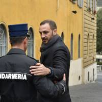 Italian journalist Emiliano Fittipaldi speaks with a gendarme as he arrives on Monday at the Vatican for the 'Vatileaks' trial of two journalists and three former Vatican officials who have been charged with leaking the documents. | AFP-JIJI