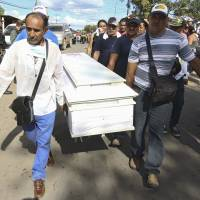 Relatives of a dead miner carry a coffin during a tribute prior to their burial in Tumeremo in Bolivar state, Venezuela, Wednesday. | REUTERS
