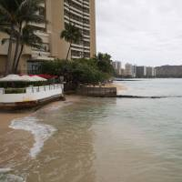 Waves can be seen lapping the foundations of an ocean-side hotel located at the west end of Honolulu's famed Waikiki Beach on Wednesday. | AP