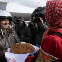 A Russian pilot who returned from Syria is welcomed with traditional bread-and-salt at an airbase near the Russian city Voronezh Tuesday. | RUSSIAN DEFENSE MINISTRY PRESS SERVICE VIA AP