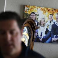 A picture of Mason Wells (photo, right) is on display as Mason Wells' father Chad Wells talks about him Tuesday in Sandy, Utah. The bombs that tore through the Brussels airport Tuesday seriously wounded three Mormon missionaries, including his son, and sent a French missionary from their group to the hospital, church officials said. | AP