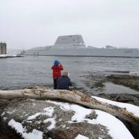 Dave Cleaveland and his son, Cody, photograph the USS Zumwalt as it passes Fort Popham at the mouth of the Kennebec River Monday in Phippsburg, Maine. The new destroyer, built at Bath Iron Works, will undergo final builder trials before the ship is presented to the Navy for inspection. | AP