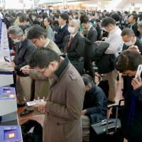 Travelers line up at check-in consoles at Haneda Airport on Tuesday morning after a glitch in ANA's reservation system glitch temporarily grounded dozens of domestic flights. | KYODO