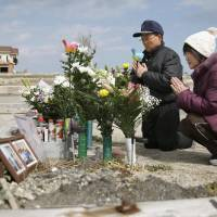 Tsutoshi Yoshida (left) and his wife, Seiko, offer prayers Friday at a site in the town of Namie, Fukushima Prefecture, where a post office used to stand. They lost their daughter Miki, who worked at the post office, in the 2011 tsunami. | KYODO