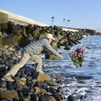 A man throws flowers into the sea at Minamisoma, Fukushima Prefecture, on Friday as he prays for victims of the 3/11 quake-tsunami disaster of 2011. | KYODO