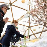 People offer prayers in front of a memorial in Tokyo's Hibiya Park on Friday to mark the fifth anniversary of the March 11, 2011, quake, tsunami and nuclear disaster. | SATOKO KAWASAKI