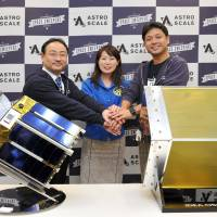 Shigeyuki Tsuchida (left), head of the Value Creation Investment Group for Innovation Network Corp. of Japan, astronaut Naoko Yamazaki (center) and Astroscale CEO Nobu Okada join hands behind their space debris technology in Tokyo on Tuesday. | YOSHIAKI MIURA