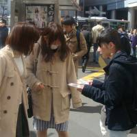 A volunteer member of the Osaka-based group Chikan Yokushi Katsudo Center distributes badges developed to warn would-be gropers on trains in Shibuya, Tokyo, on Friday. | DAISUKE KIKUCHI