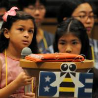 Lailah Aziz, 8, from Bechtel Elementary School in Okinawa, pauses to think before spelling a word during the 7th Japan Times Bee in Tokyo on Saturday. | SATOKO KAWASAKI