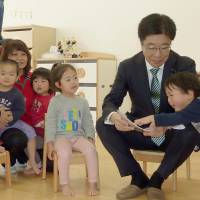 Katsunobu Kato, state minister in charge of building a society in which all 100 million people can play an active role, visits a nursery school in the city of Osaka on Saturday.   KYODO