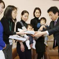 Yasuhisa Shiozaki, Japan's minister of health, labor and welfare, receives documents from a group of mothers in Tokyo on Wednesday that contain about 28,000 signatures from people seeking a better child care system in the country after they were inspired by an anonymous blog post written by a frustrated mother. | KYODO