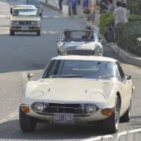 A Toyota 2000GT and other classic cars parade through the Odaiba waterfront district in Tokyo in November 2013. | KYODO