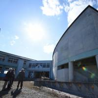 Participants in a 'dark tourism' tour check out vacant Ukedo Elementary School in the abandoned town of Namie, Fukushima Prefecture, in early February. As the fifth anniversary of the 2011 calamity approaches, a growing number of visitors are taking part in Fukushima-related tours. | AFP-JIJI