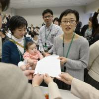 A group of working mothers hands a petition to lawmakers during a rally outside the Diet on March 23 calling for capacity levels for children at day-care centers to be raised. | KYODO