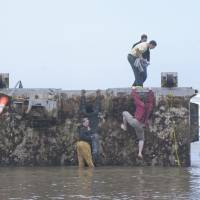This photo, taken June 7, 2012, shows local people in Newport, Oregon, clambering onto a floating dock that was swept away from the port of Misawa, Aomori Prefecture, in the March 2011 tsunami. | LYNN KETCHUM, OREGON STATE UNIVERSITY/KYODO