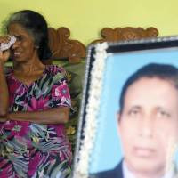 Magret Fernando cries next to an image of her husband Niculas Fernando, who died at the Tokyo Regional Immigration Bureau, in Chilaw on Nov. 10, 2015. | REUTERS