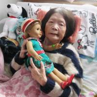 Tsuyako Matsumoto holds a doll in her bed in Kitami, Hokkaido, on Wednesday. The doll was gifted by U.S. Ambassador to Japan Caroline Kennedy. | KYODO