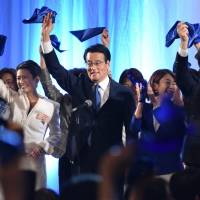 Katsuya Okada (center), leader of the newly formed Democratic Party, and other members of what is now Japan's largest opposition party, wave blue handkerchiefs during its inauguration ceremony in Tokyo on Sunday. | AFP-JIJI