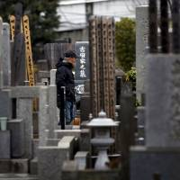A man walks between gravestones in Tokyo on March 5. Despite its rapidly graying population, Japan has no laws on 'living wills,' let alone assisted suicide, which is legal in such states as California and nations including Canada and Belgium. | REUTERS