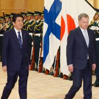 Finnish President Sauli Niinisto and Prime Minister Shinzo Abe review a guard of honor prior to their meeting at the Prime Minister's Office in Tokyo on Thursday. | AFP-JIJI