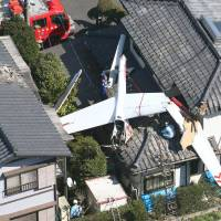 A glider is seen between two houses in the town of Sakae, Chiba Prefecture, after a crash which killed two men. | KYODO