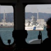 The captain of the Greenpeace yacht Rainbow Warrior III, Peter Wilcox, pilots his ship past the troubled Fukushima No. 1 nuclear power plant on Feb. 22. | AFP-JIJI