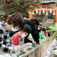 Adults and children participate in an event to set a record for the longest line of green tea dumplings in the city of Uji, Kyoto Prefecture, on Sunday. A Guinness World Record's official confirmed the line of dumplings, at 341.57 meters, was the world's longest. | KYODO